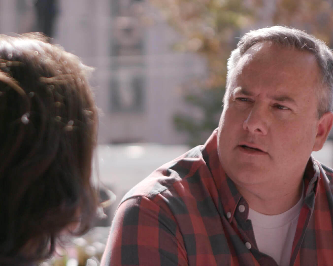 Man In a Red And Black Plaid Shirt Talking To a Woman Outside